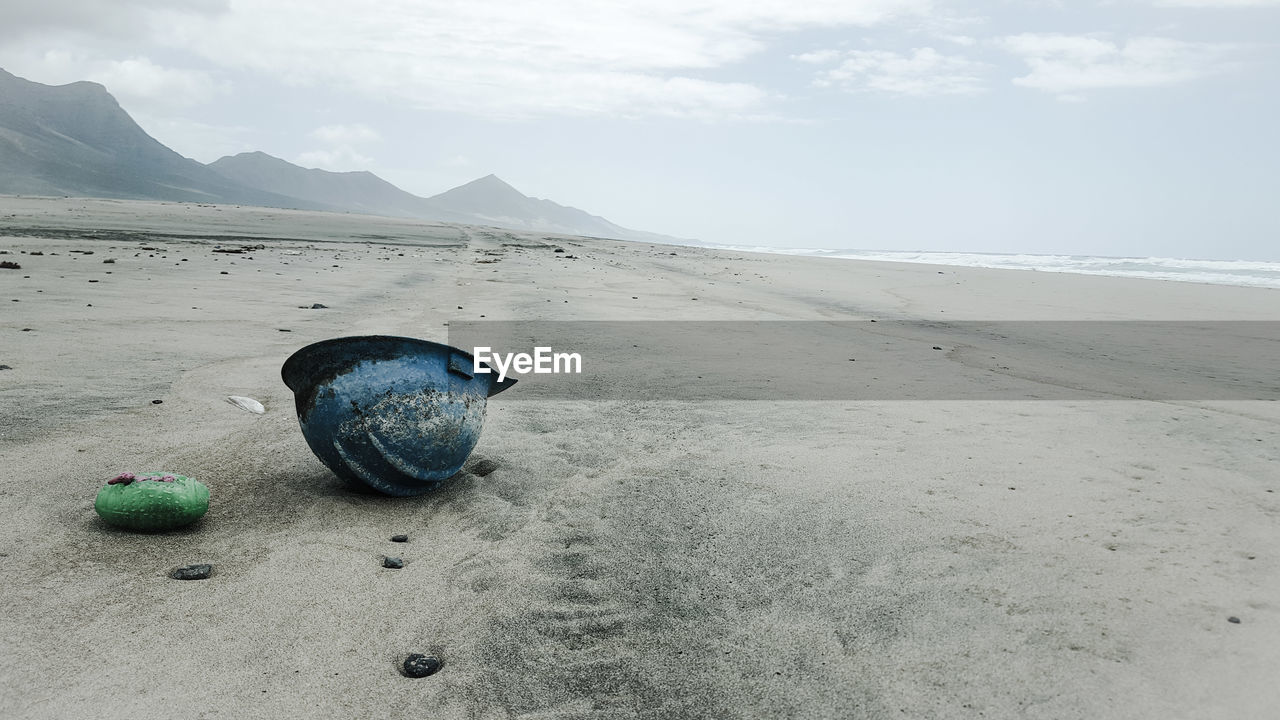 Abandoned Hardhat On Sandy Beach