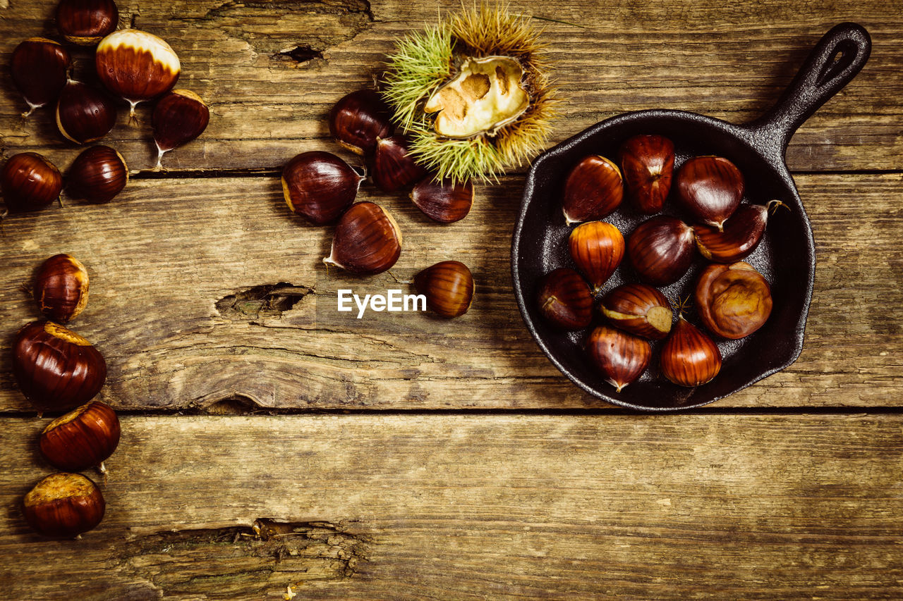 food and drink, food, healthy eating, table, freshness, wellbeing, still life, fruit, wood - material, nut, indoors, nut - food, directly above, chestnut - food, high angle view, chestnut, large group of objects, no people, brown, bowl