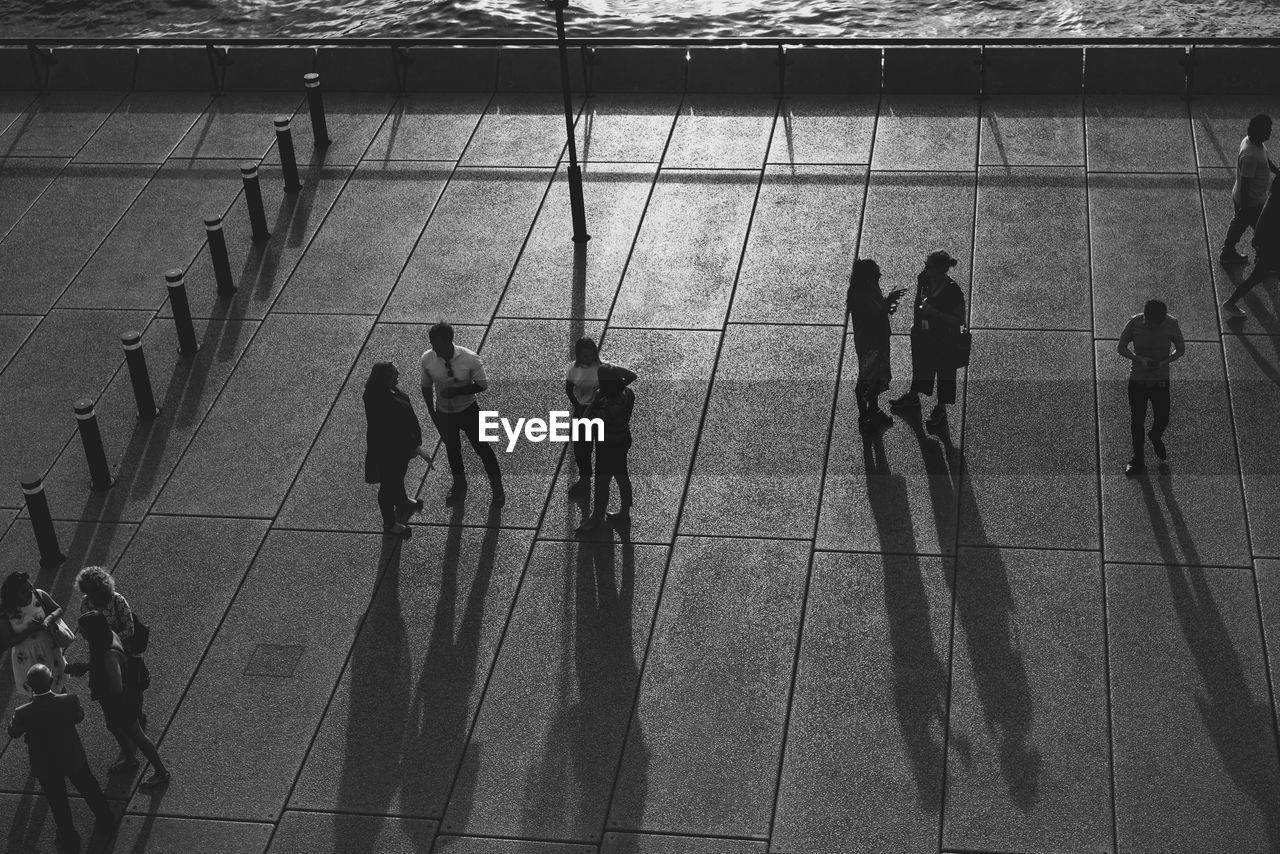 group of people, real people, men, medium group of people, high angle view, people, lifestyles, group, full length, architecture, women, adult, walking, leisure activity, crowd, day, built structure, reflection, shadow, outdoors, tiled floor