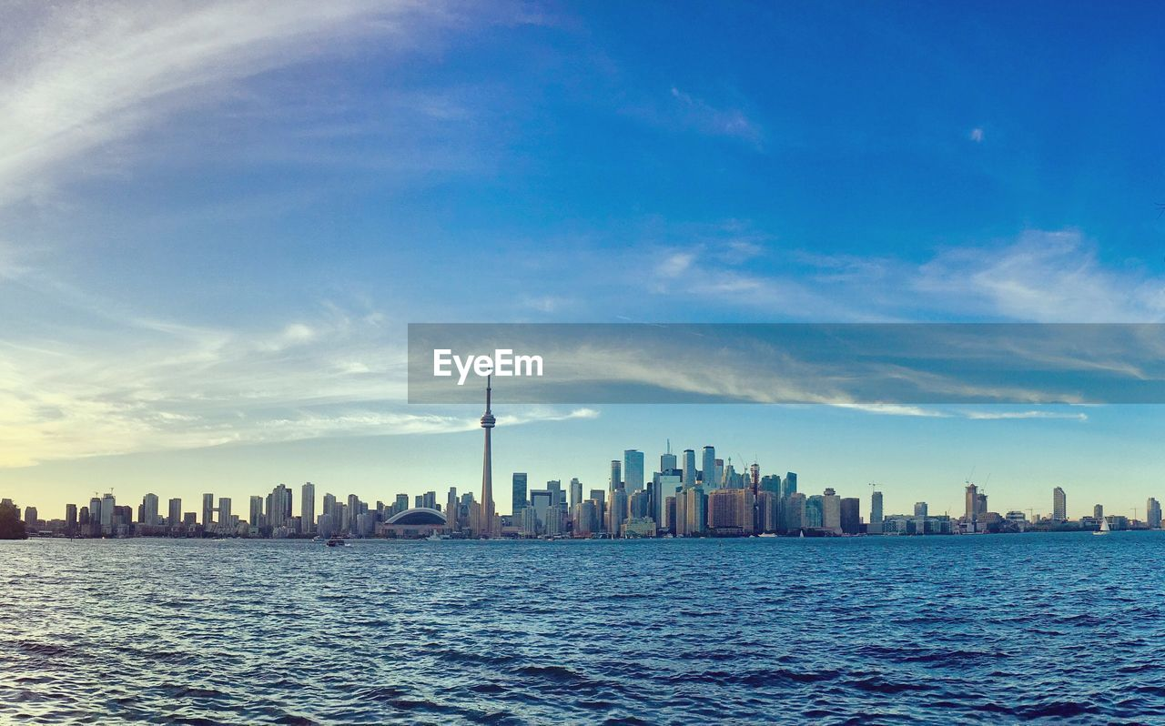 sky, building, architecture, built structure, building exterior, city, water, office building exterior, skyscraper, landscape, urban skyline, tall - high, waterfront, cloud - sky, cityscape, tower, nature, sea, no people, modern, financial district, outdoors, spire