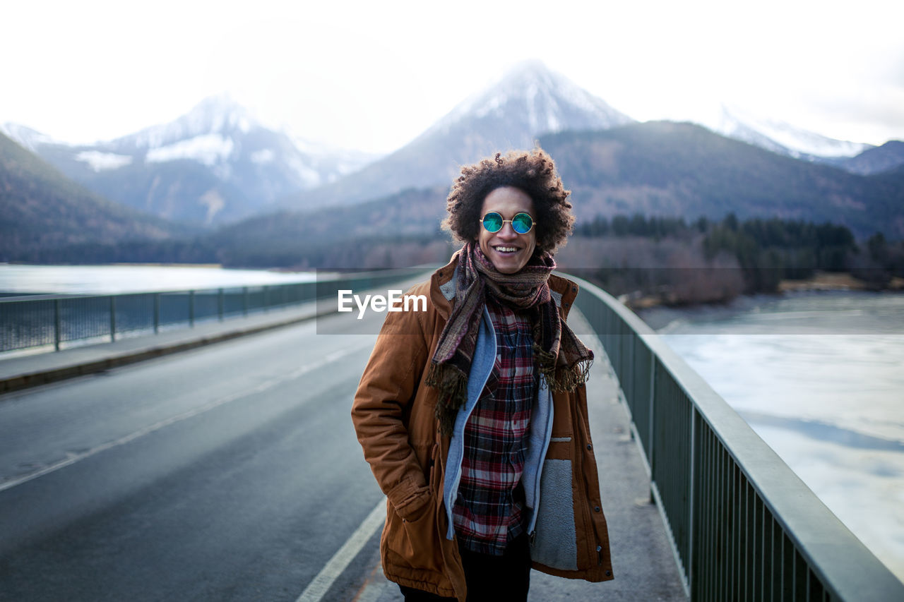 mountain, winter, looking at camera, portrait, one person, real people, young adult, standing, front view, cold temperature, lifestyles, warm clothing, nature, smiling, leisure activity, scenics - nature, clothing, beauty in nature, mountain range, outdoors