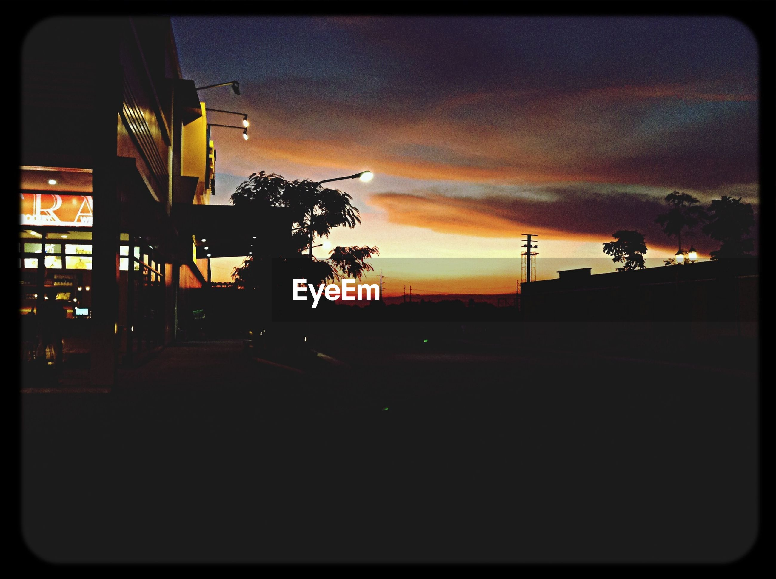 sunset, transfer print, silhouette, sky, built structure, architecture, auto post production filter, building exterior, tree, cloud - sky, dusk, orange color, dark, cloud, outdoors, low angle view, no people, nature, city, cloudy