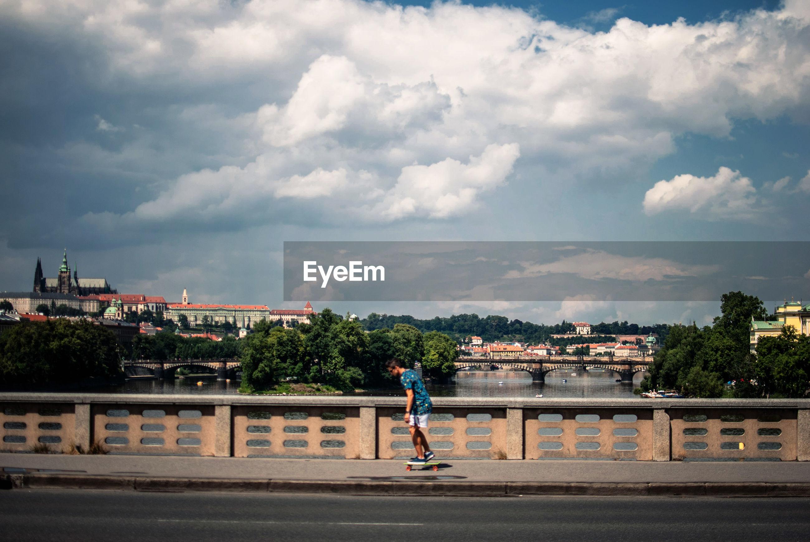Mid distance view of man skateboarding on sidewalk at bridge against cloudy sky