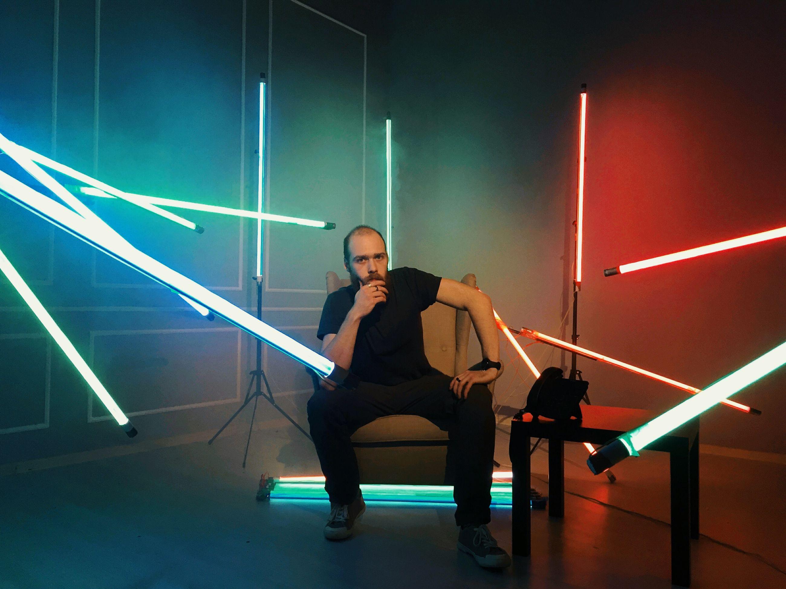 Portrait of man sitting in illuminated room