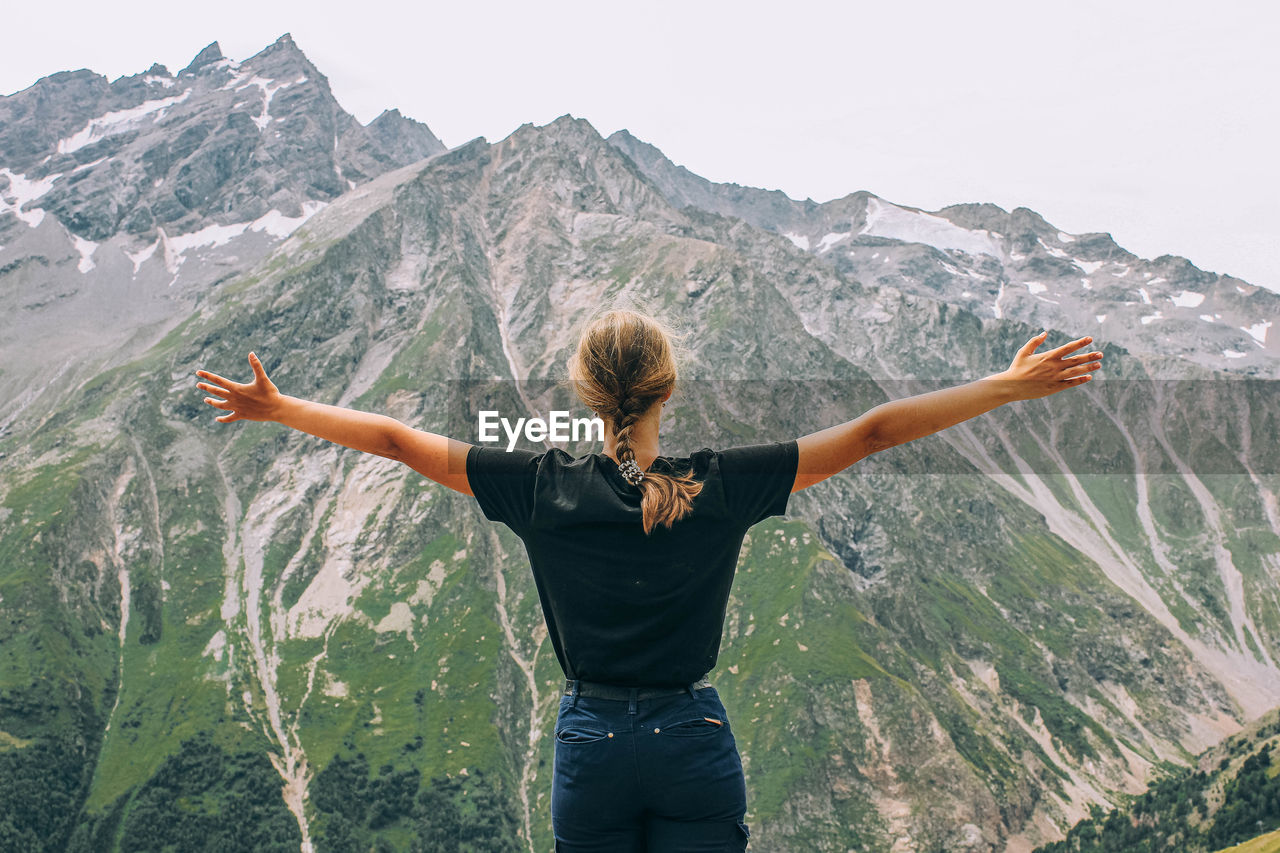 REAR VIEW OF WOMAN WITH ARMS RAISED STANDING ON MOUNTAINS