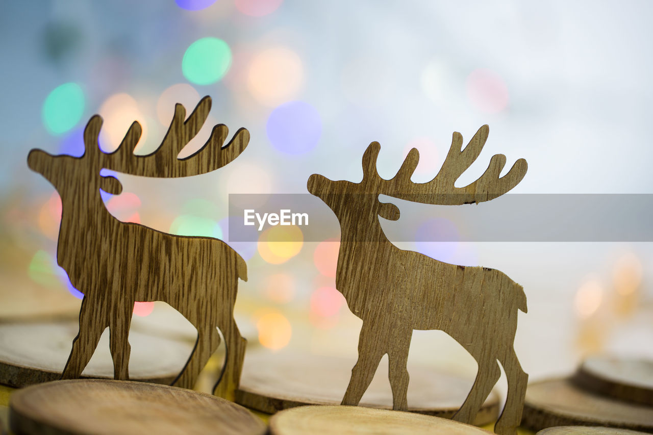 animal representation, no people, representation, sky, art and craft, wood - material, creativity, close-up, animal, focus on foreground, lens flare, deer, sculpture, nature, day, still life, decoration, animal wildlife, mammal, reindeer