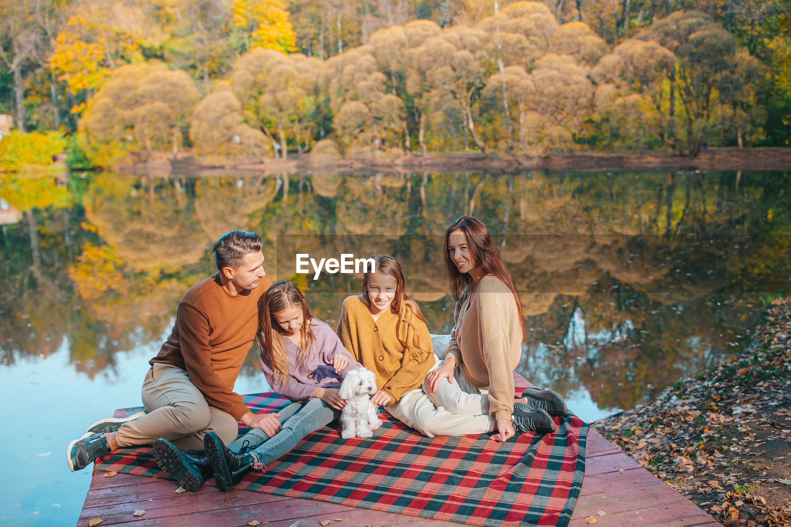 GROUP OF PEOPLE SITTING IN AUTUMN