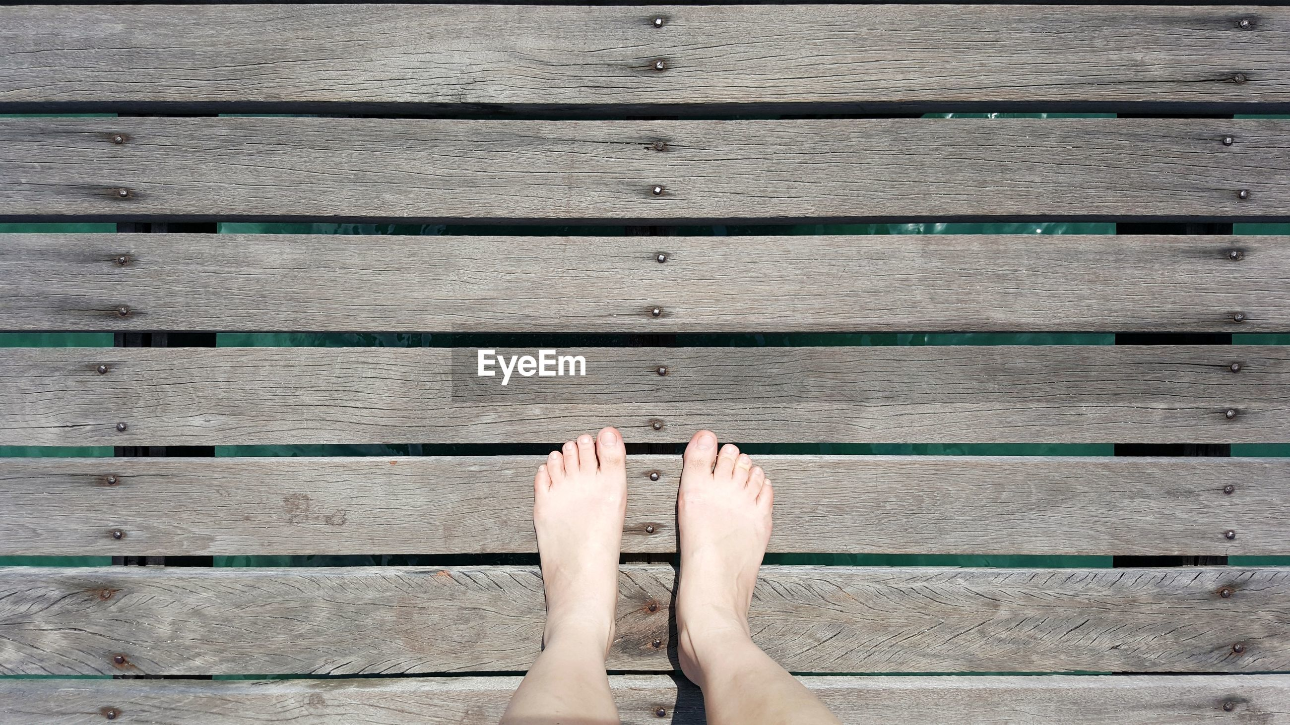 Low section of person legs on pier