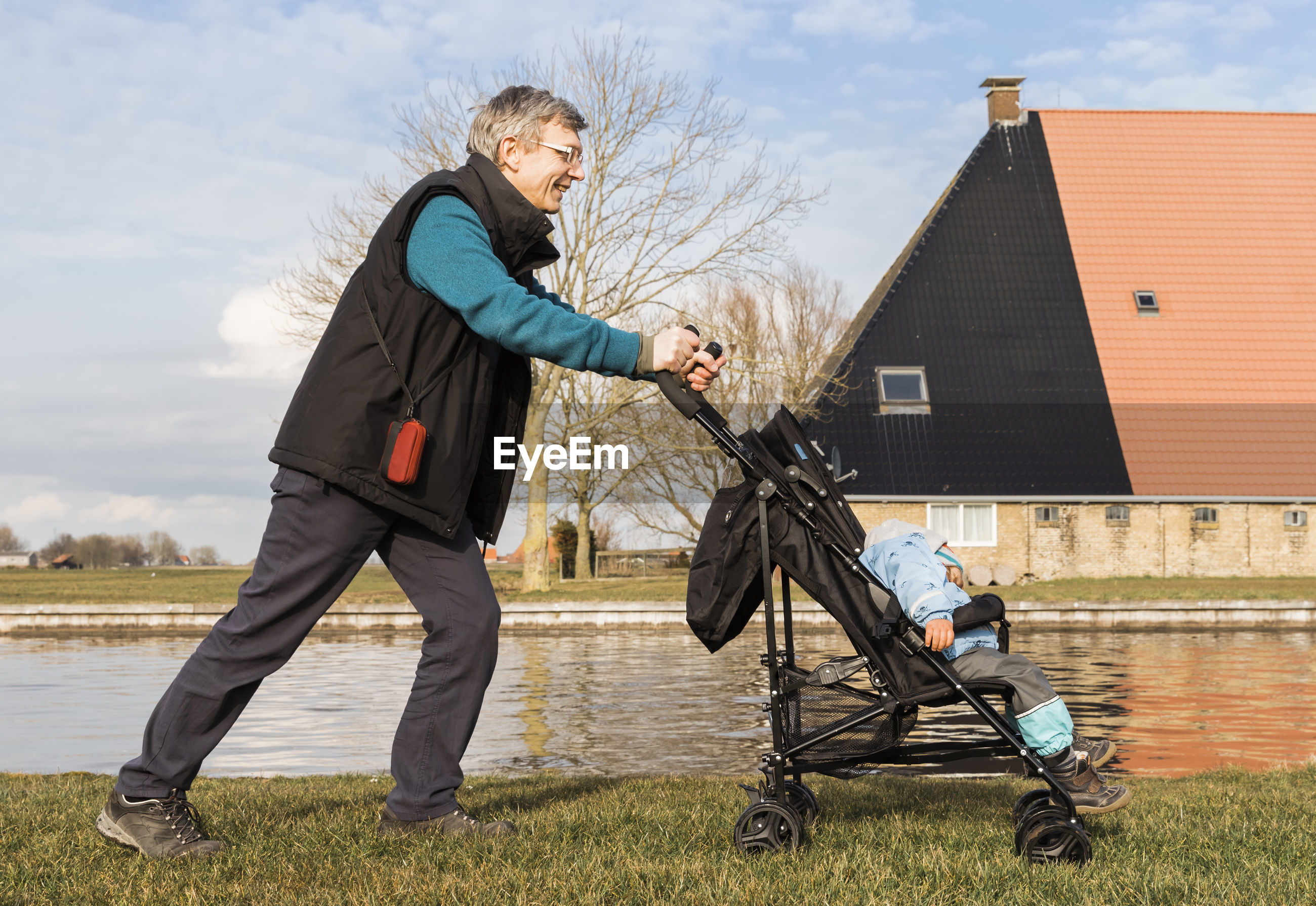 Side view of grandfather pushing baby stroller on field by lake