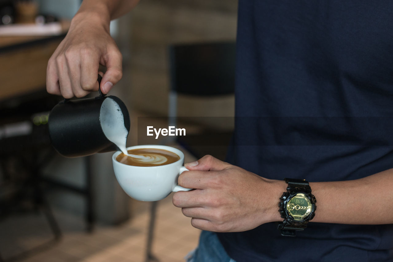 Midsection of barista pouring milk in coffee cup at cafe
