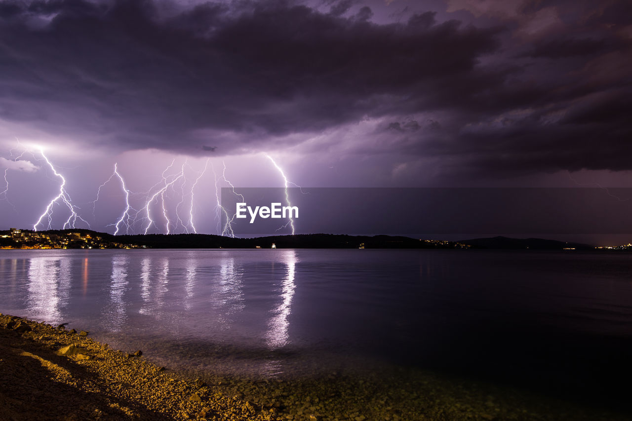 Thunderstorms In Cloudy Sky Over Lake At Night