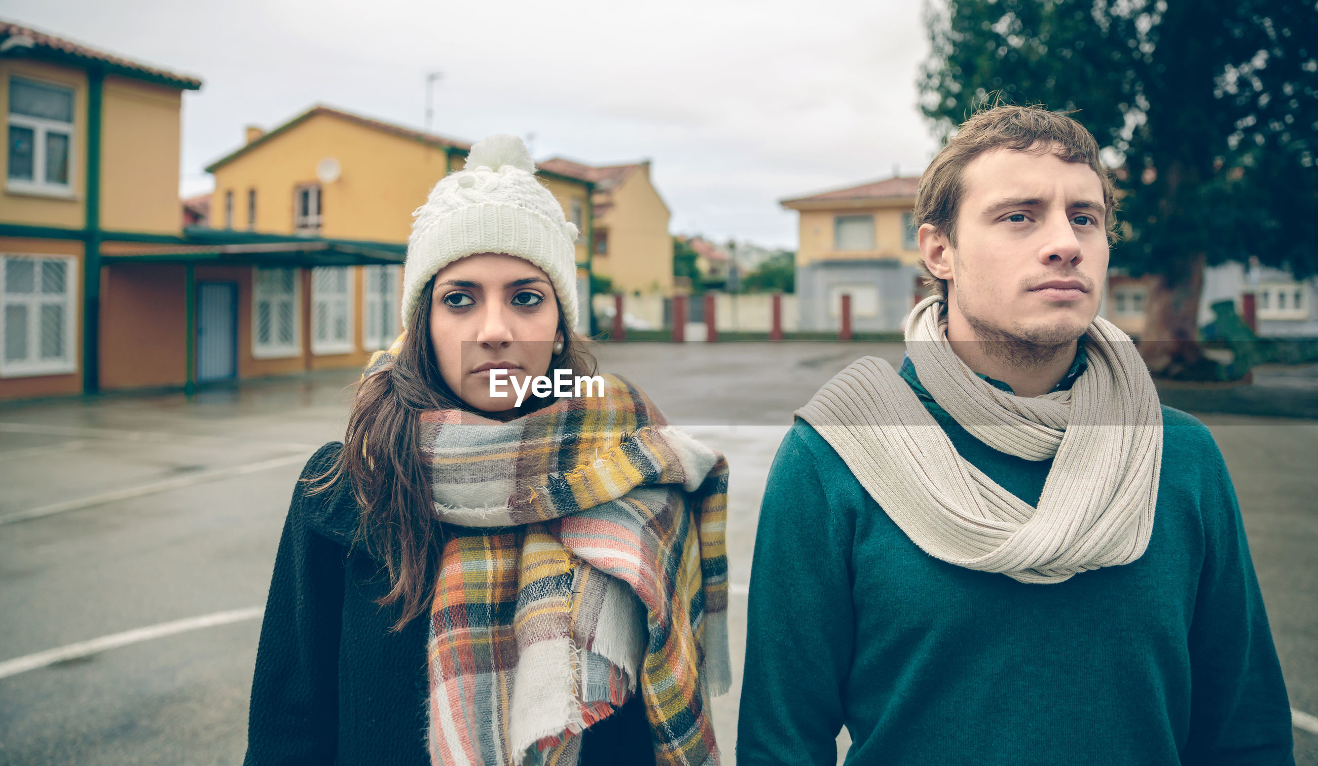 Sad couple looking away while standing on road