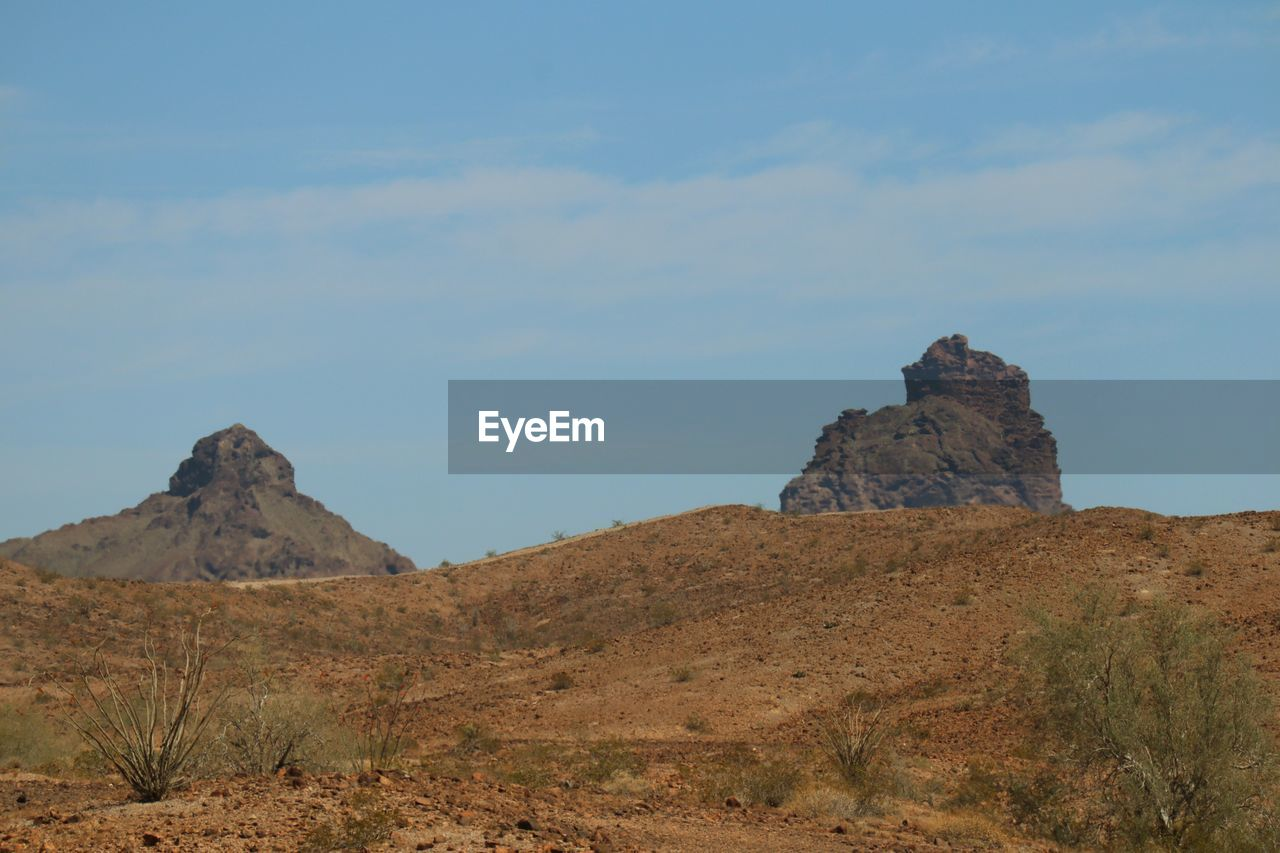 sky, environment, rock, land, mountain, landscape, nature, beauty in nature, tranquility, rock formation, travel, tranquil scene, rock - object, remote, no people, non-urban scene, scenics - nature, solid, outdoors, day, climate, arid climate, mountain peak, formation, eroded