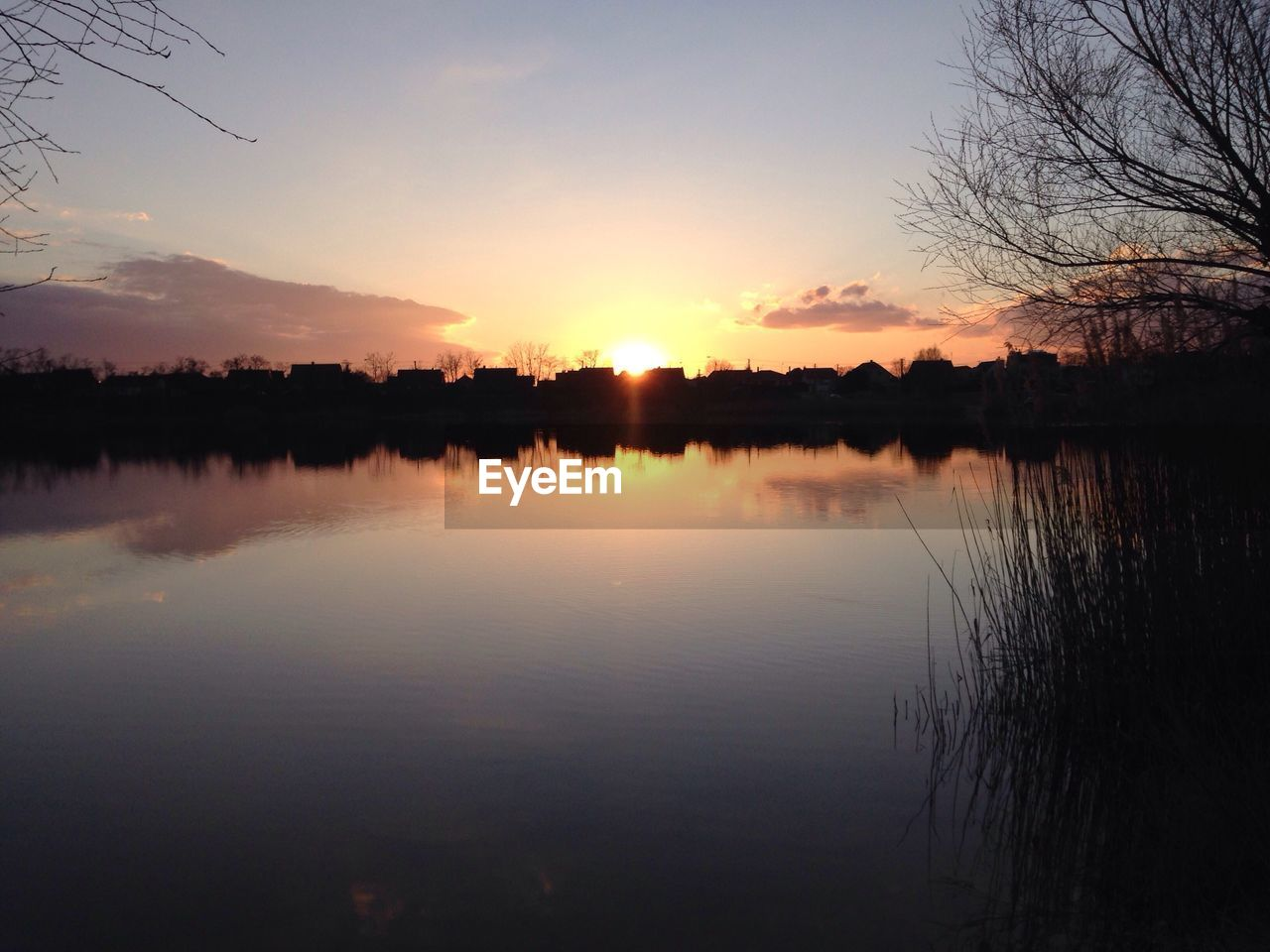 sunset, reflection, beauty in nature, nature, tranquil scene, water, scenics, lake, tranquility, idyllic, silhouette, sky, orange color, standing water, non-urban scene, outdoors, no people, tree, waterfront