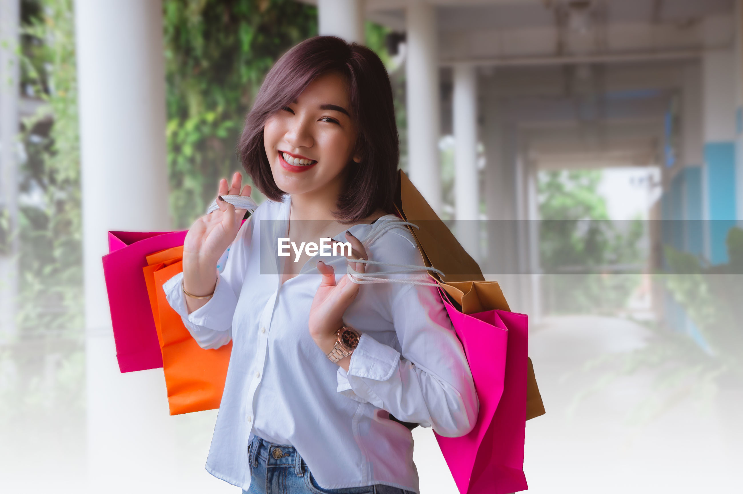 Portrait of smiling young woman with shopping bags standing outdoors