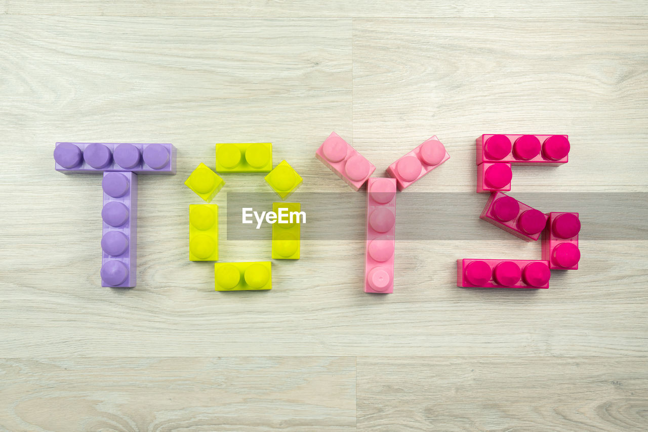 Close-Up Of Text Made With Colorful Toy Blocks On Table