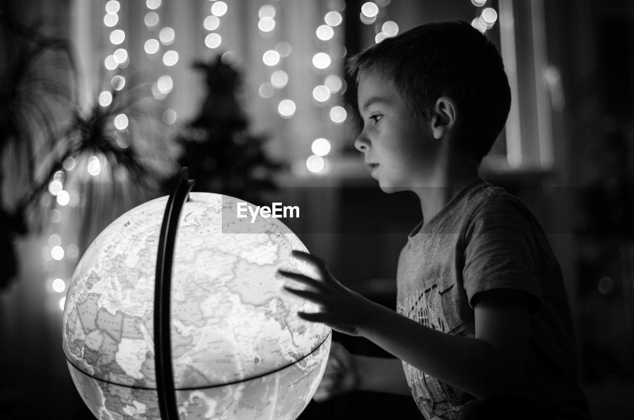 Boy touching world map globe at night