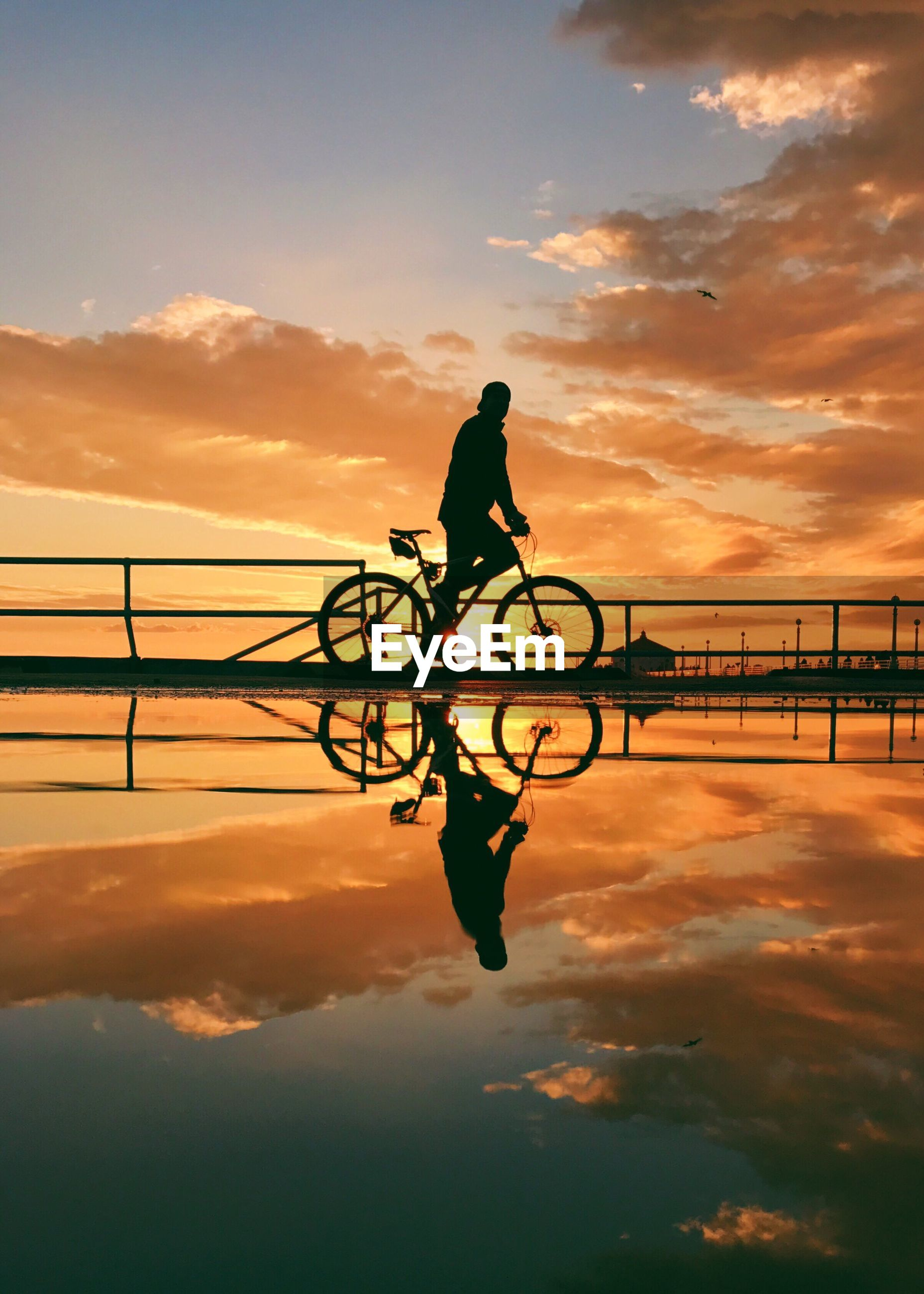 Silhouette man cycling with reflection in lake against sky during sunset