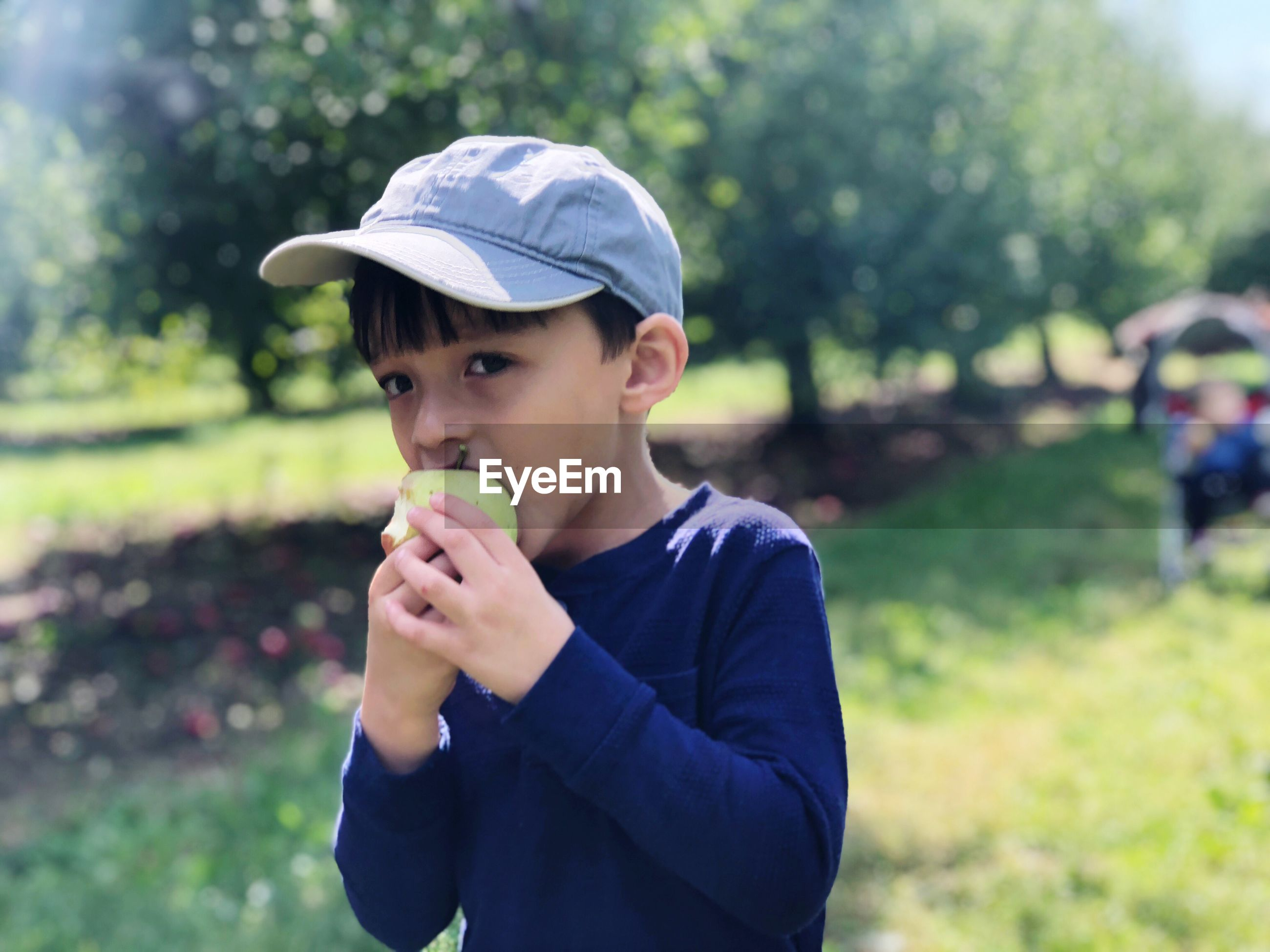 Boy eating apple while standing on field