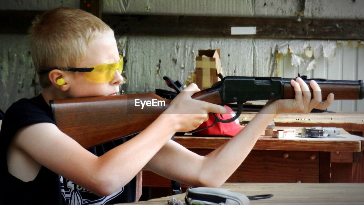Boy Practicing With Rifle At Shooting Range