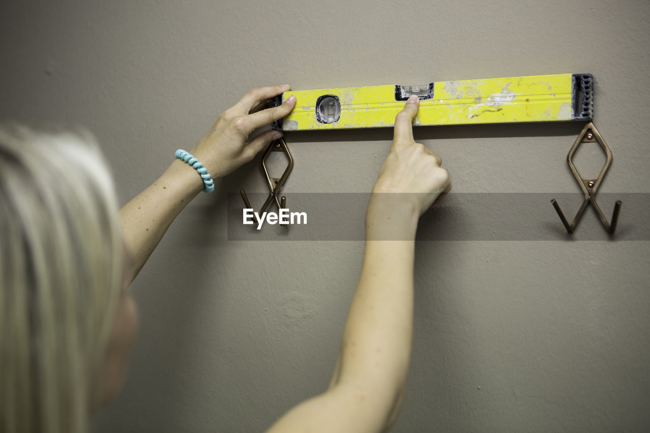 Rear view of woman holding yellow spirit level on wall