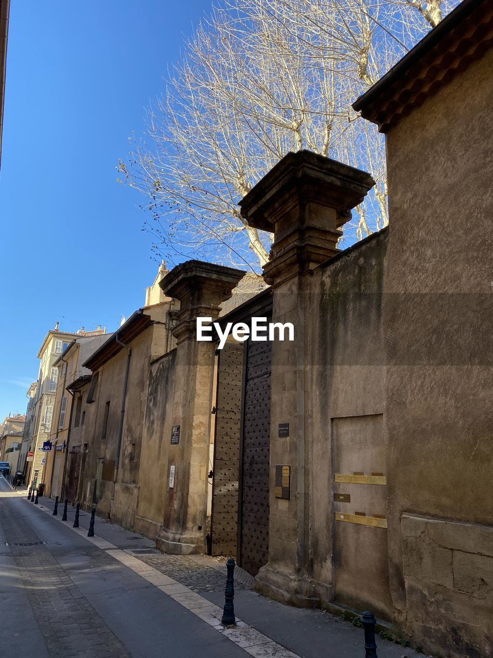 architecture, built structure, building exterior, sky, building, nature, day, clear sky, blue, sunlight, residential district, old, outdoors, street, tree, city, house, the past, history, one person