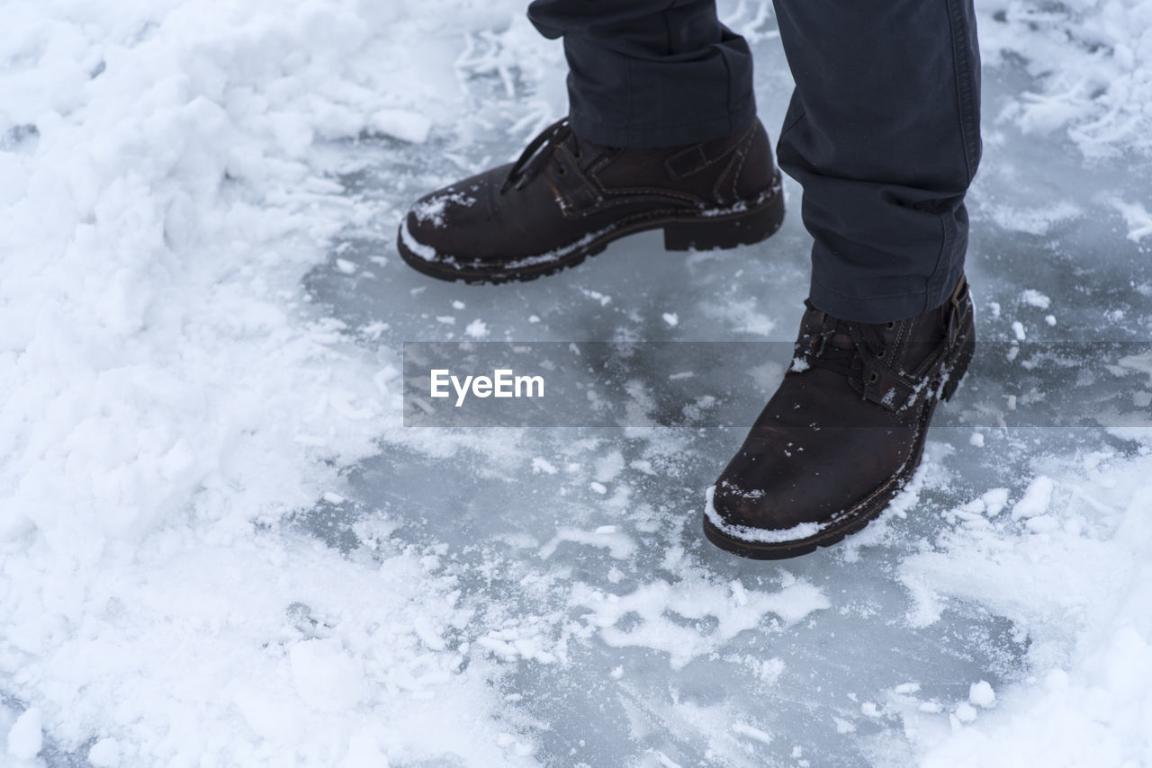 Low section of man walking on snow