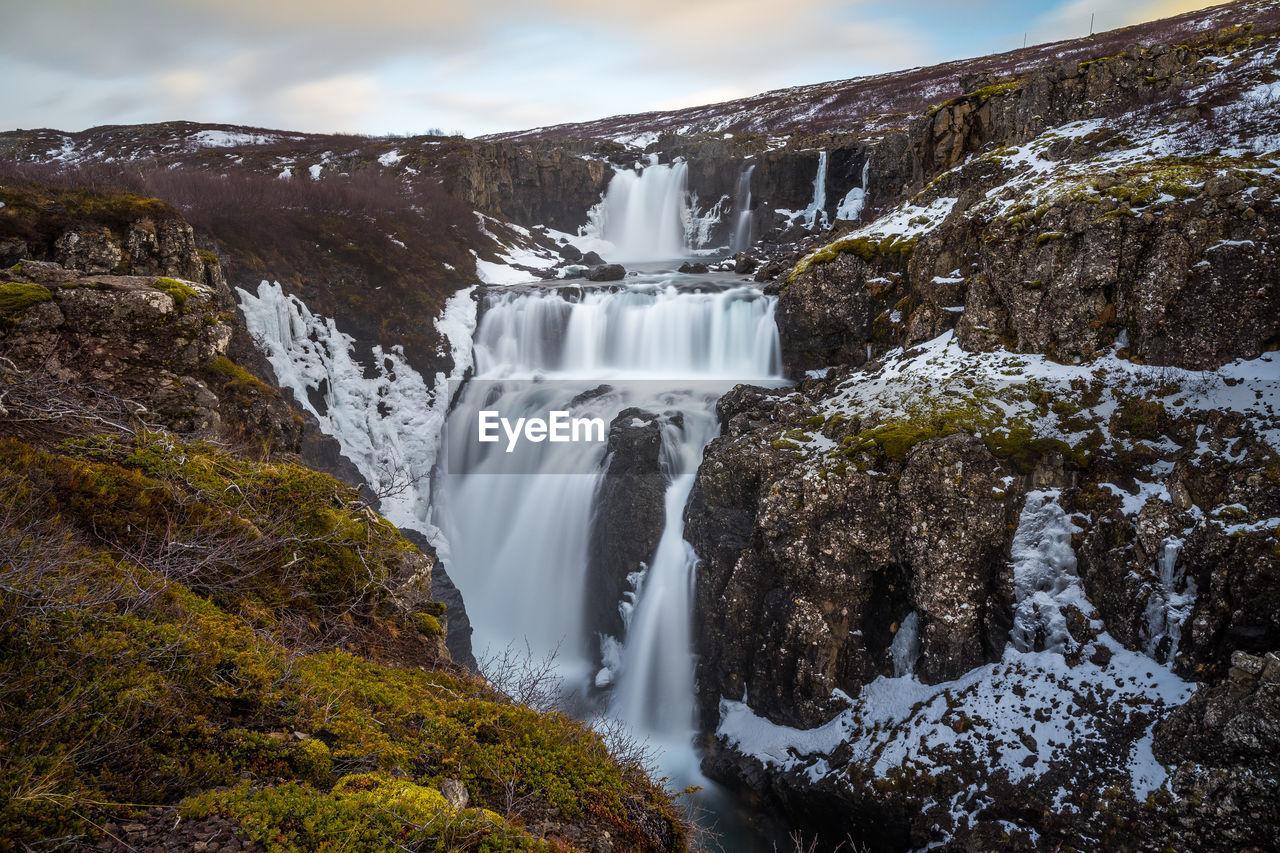 VIEW OF WATERFALL AGAINST ROCKS