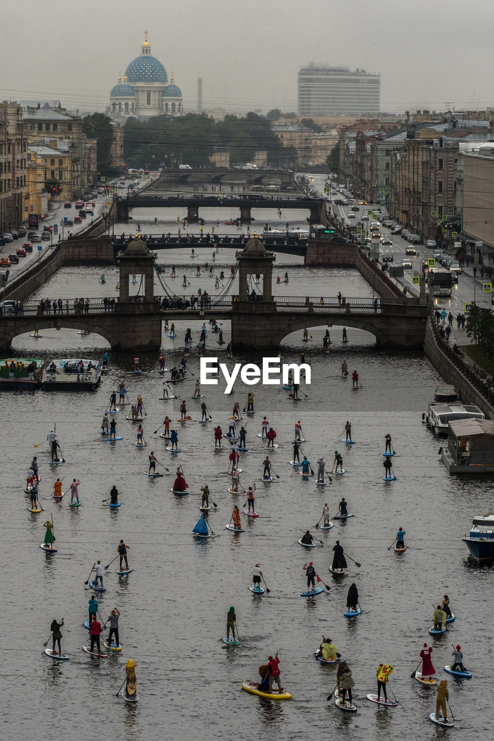High angle view of people paddleboarding in river against buildings