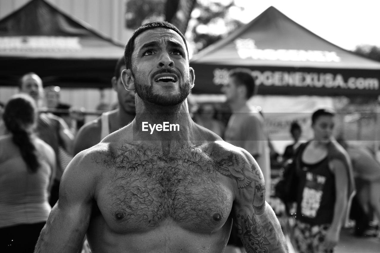 Worried Shirtless Man Looking Up At Carnival