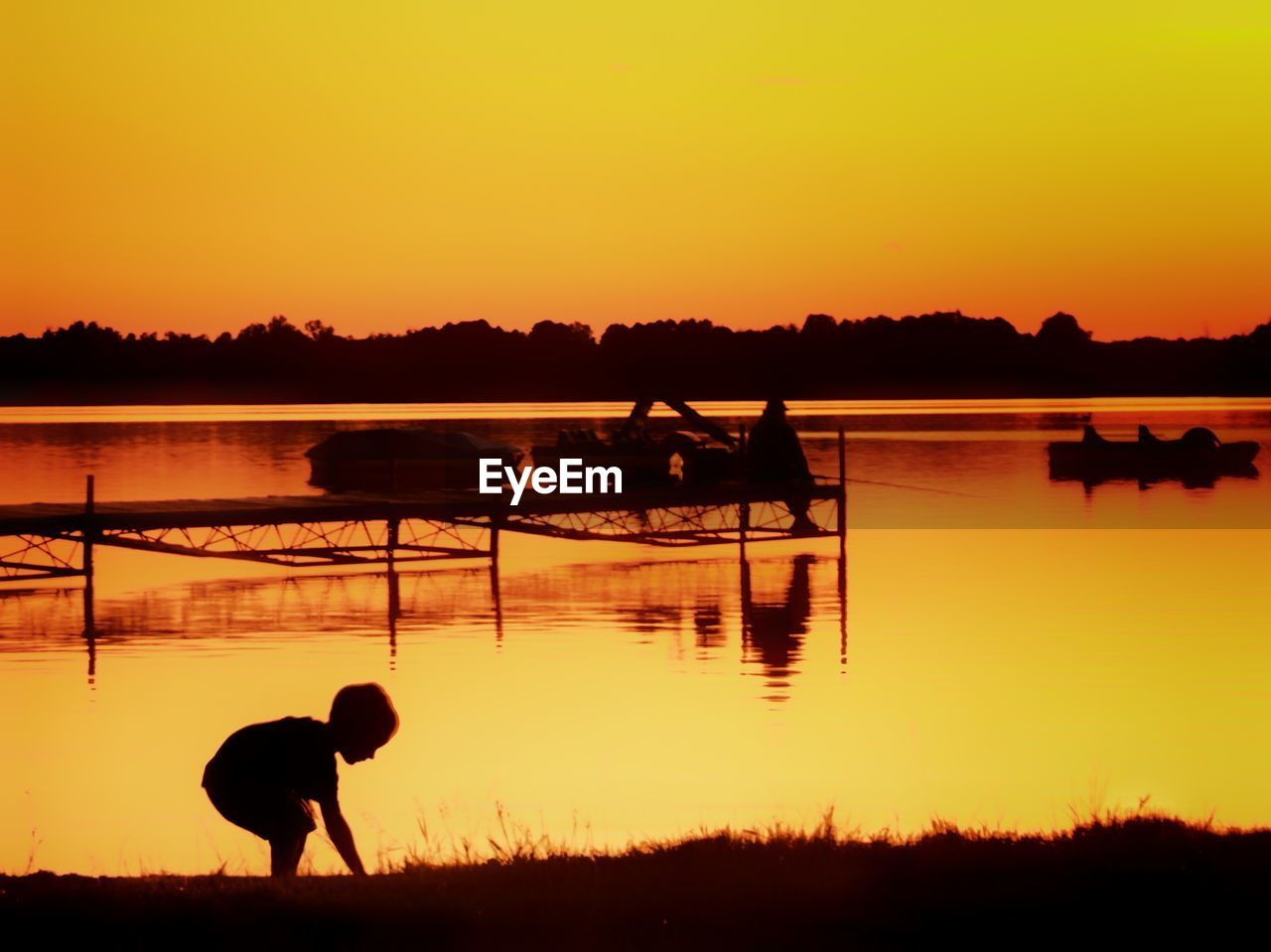 sunset, silhouette, water, orange color, reflection, nature, beauty in nature, lake, tranquility, scenics, outdoors, tranquil scene, sky, men, one person, real people, clear sky, tree, full length, farmer, nautical vessel, day, people