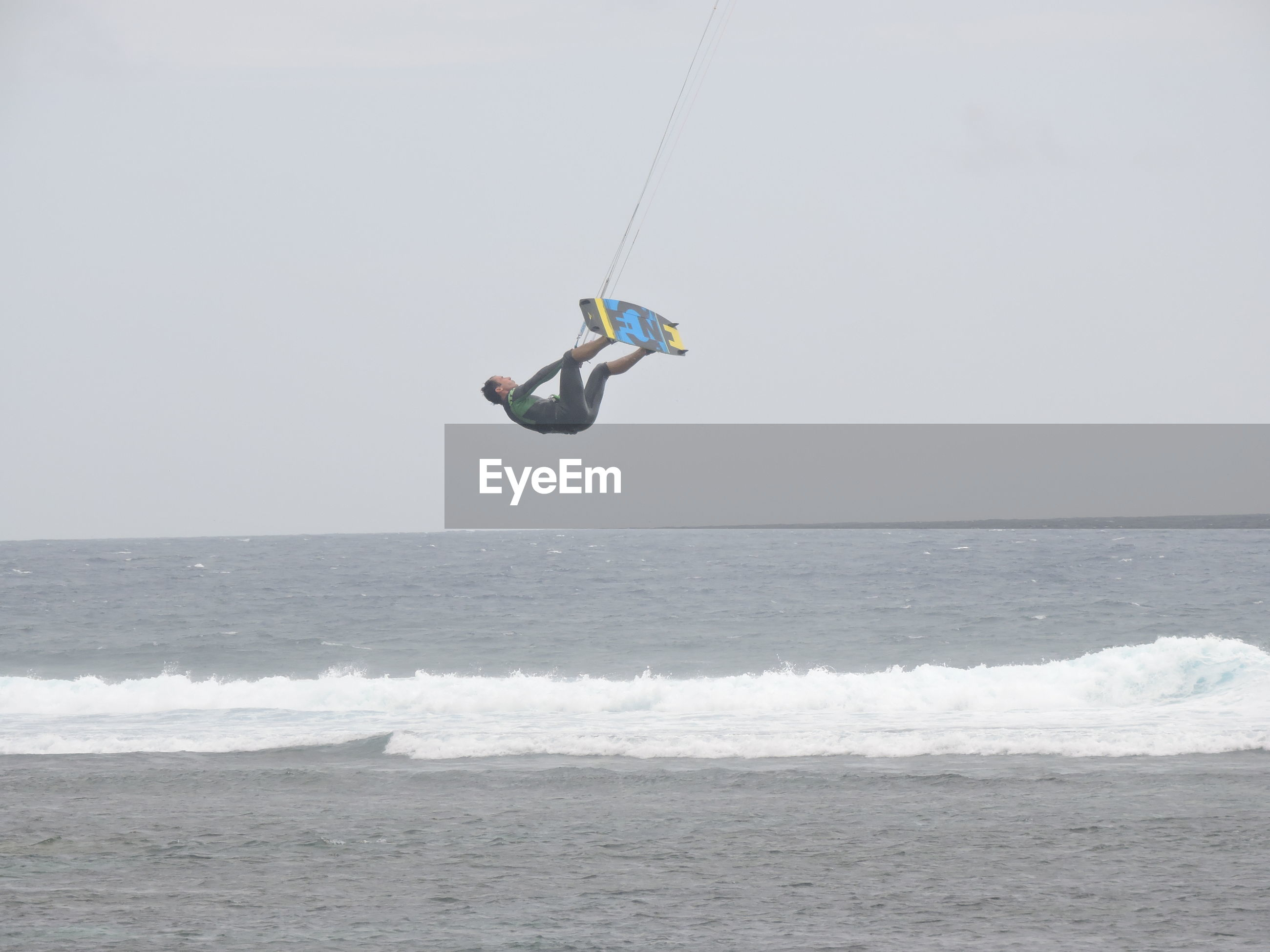 sea, mid-air, lifestyles, leisure activity, water, real people, full length, jumping, horizon over water, extreme sports, kiteboarding, one person, adventure, day, outdoors, men, sky, scenics, sport, nature, beauty in nature, beach, parachute
