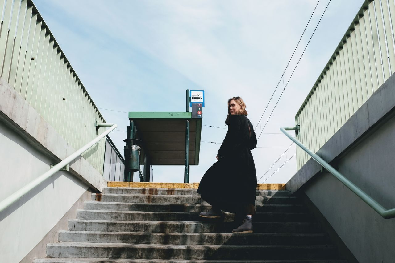 Low angle view of woman standing on staircase against sky