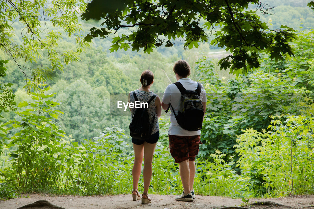 rear view, full length, plant, tree, casual clothing, nature, day, women, green color, adult, walking, two people, leisure activity, growth, togetherness, people, real people, young adult, lifestyles, footpath, outdoors, hairstyle, shorts, teenager