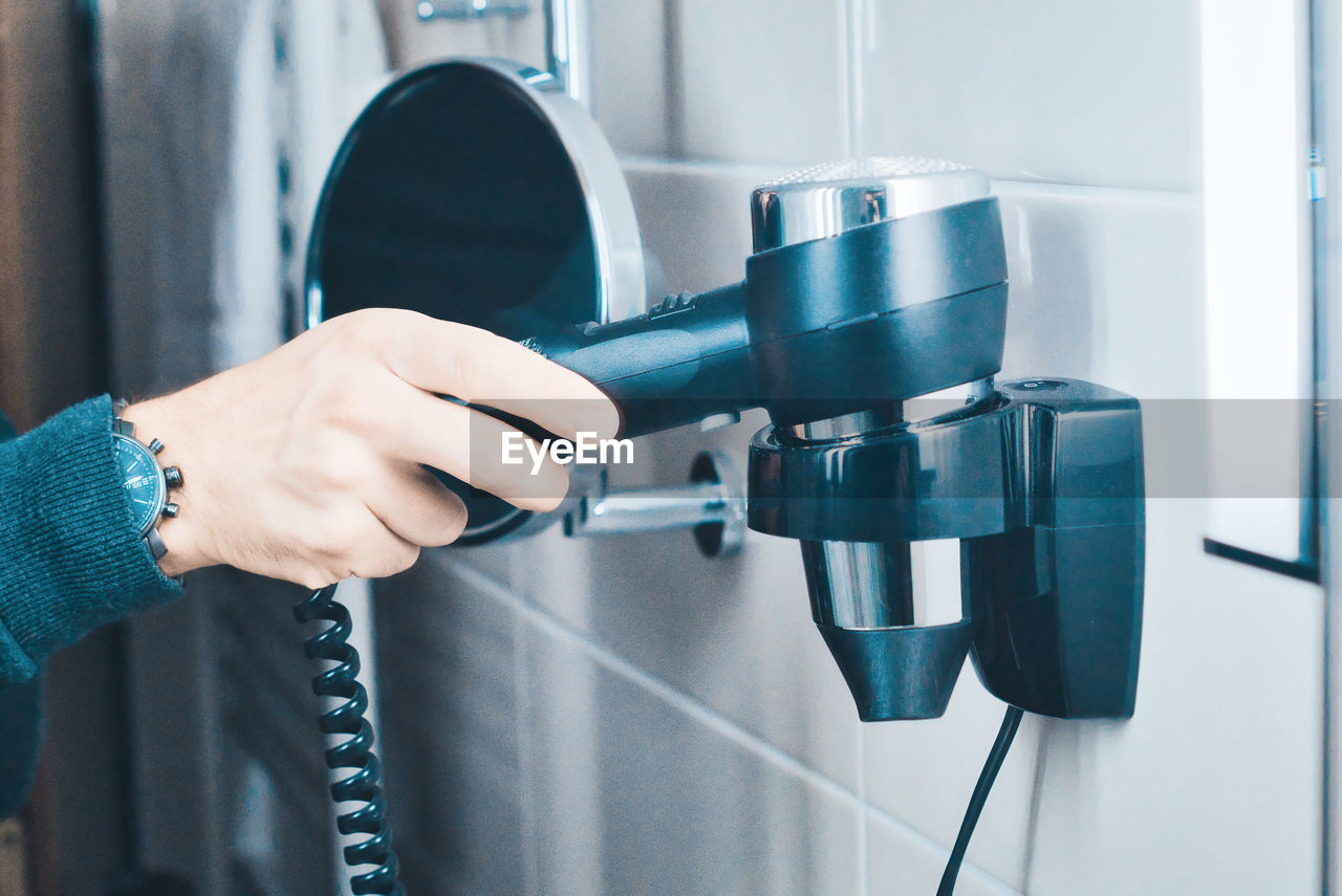 Midsection of woman holding hair dryer in bathroom