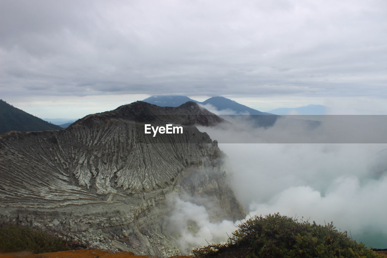 Scenic View Of Volcanic Mountains Against Cloudy Sky