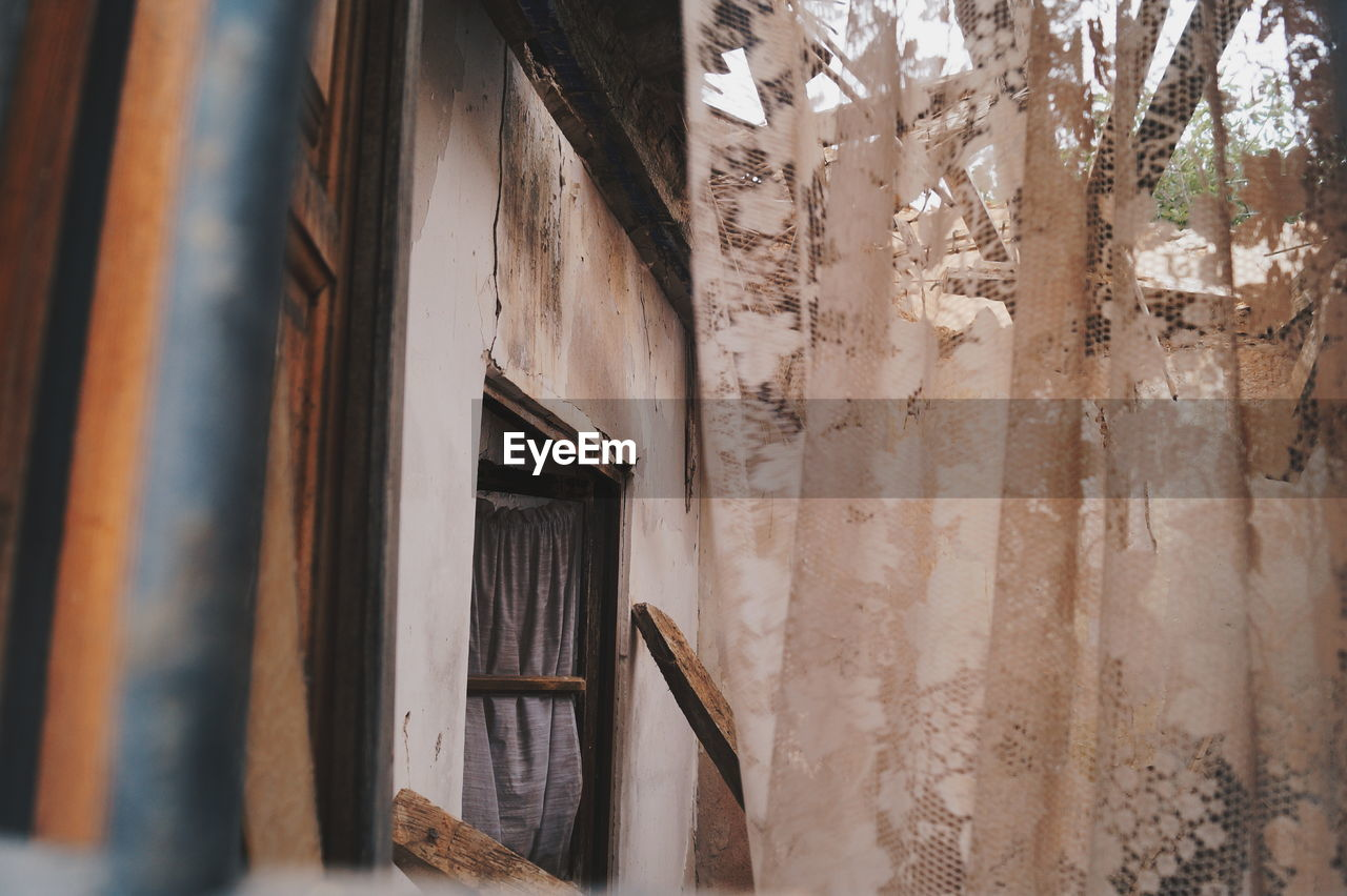 architecture, no people, built structure, indoors, building, window, old, curtain, wood - material, day, weathered, damaged, low angle view, house, wall - building feature, abandoned, history, the past, selective focus, deterioration, ruined