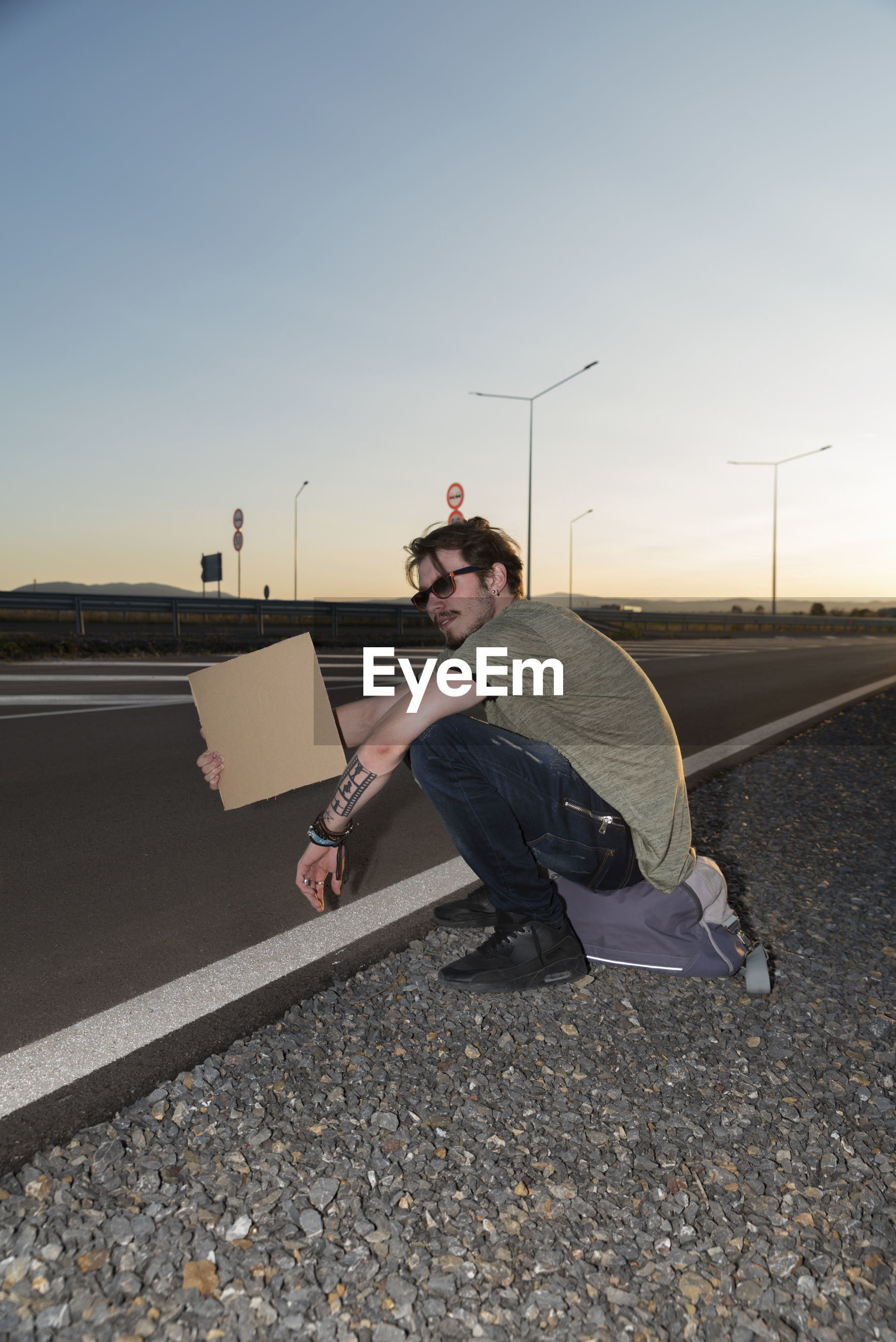 MAN SITTING ON ROAD WITH UMBRELLA