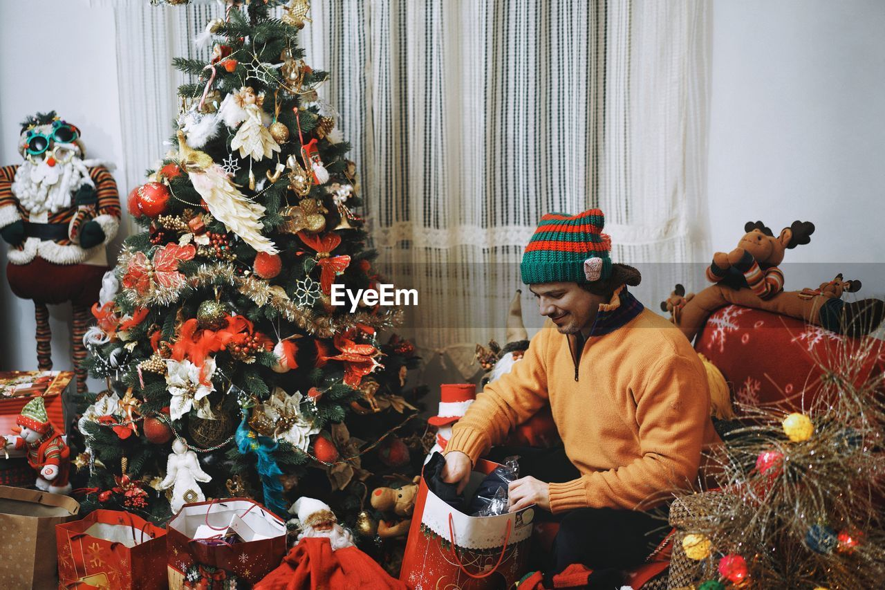 Man With Gifts By Christmas Tree