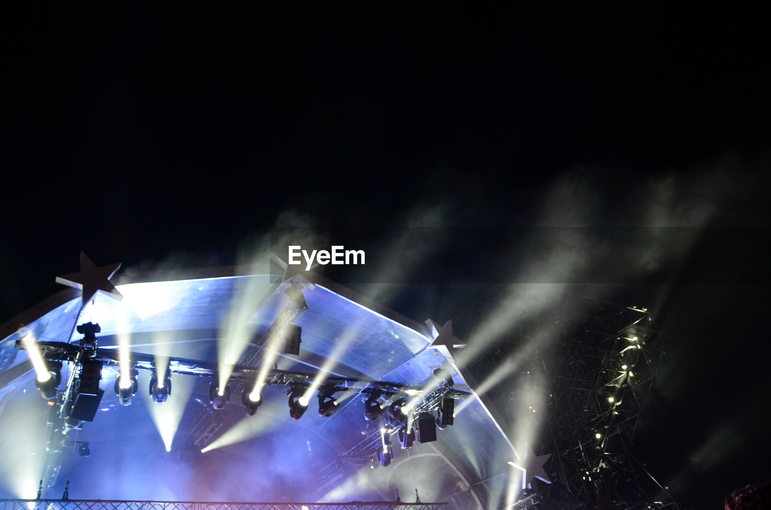 Low angle view of illuminated stage lights against sky at night