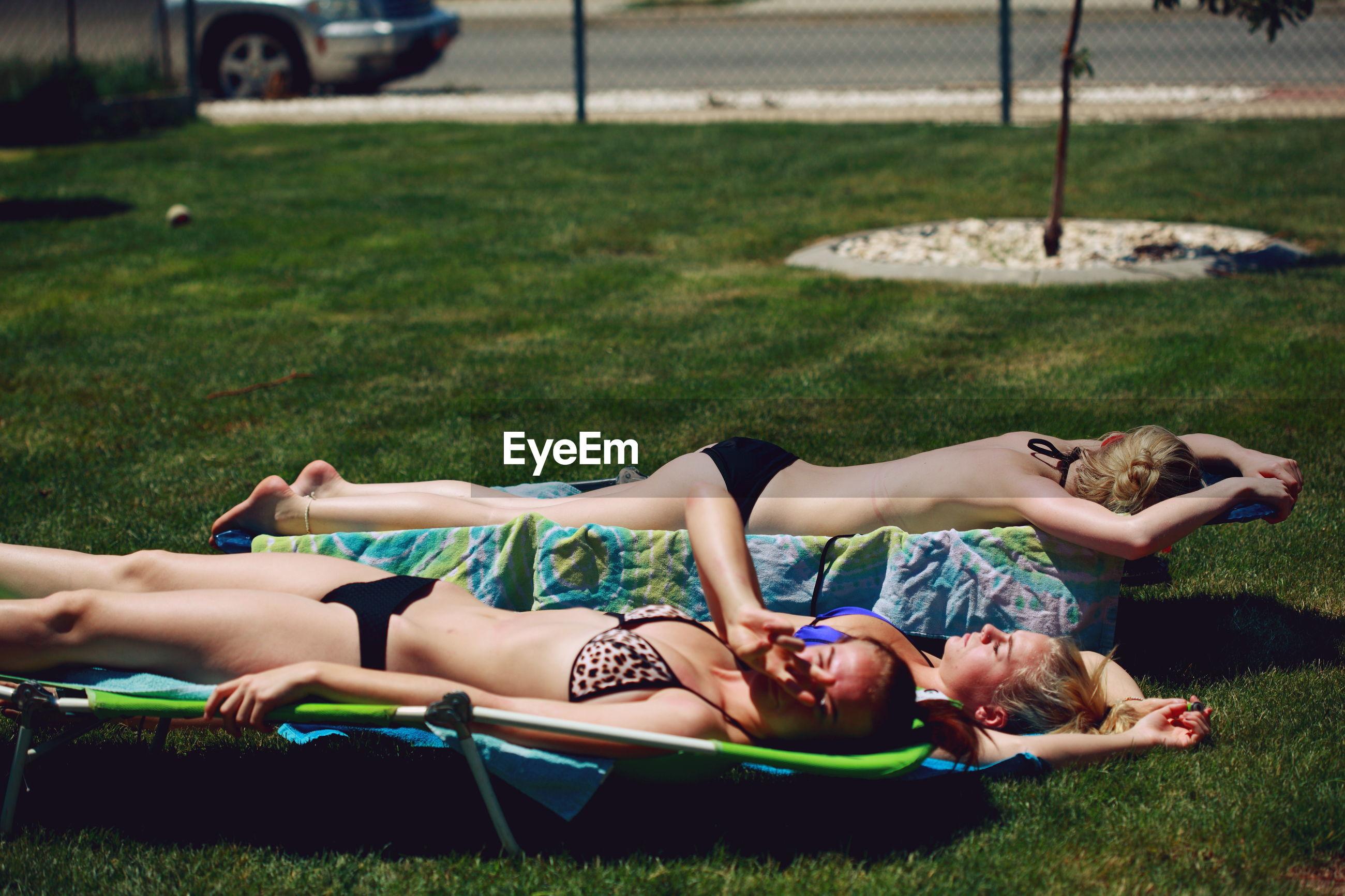 Friends sunbathing on grassy field in yard