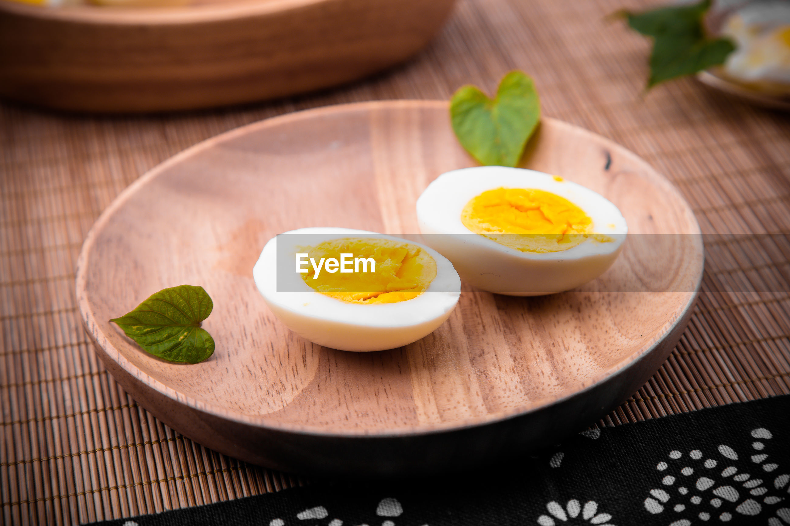 Close-up of boiled egg in wooden plate on table