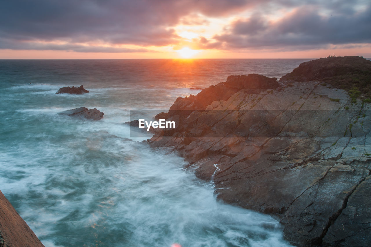 sky, beauty in nature, sunset, sea, scenics - nature, cloud - sky, water, rock, horizon over water, beach, idyllic, horizon, land, tranquil scene, rock - object, nature, solid, no people, tranquility, outdoors