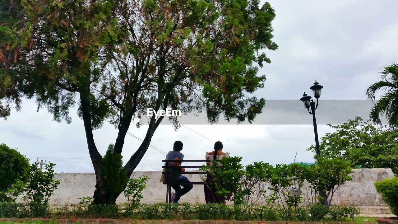 Rear view of couple sitting on bench against sky