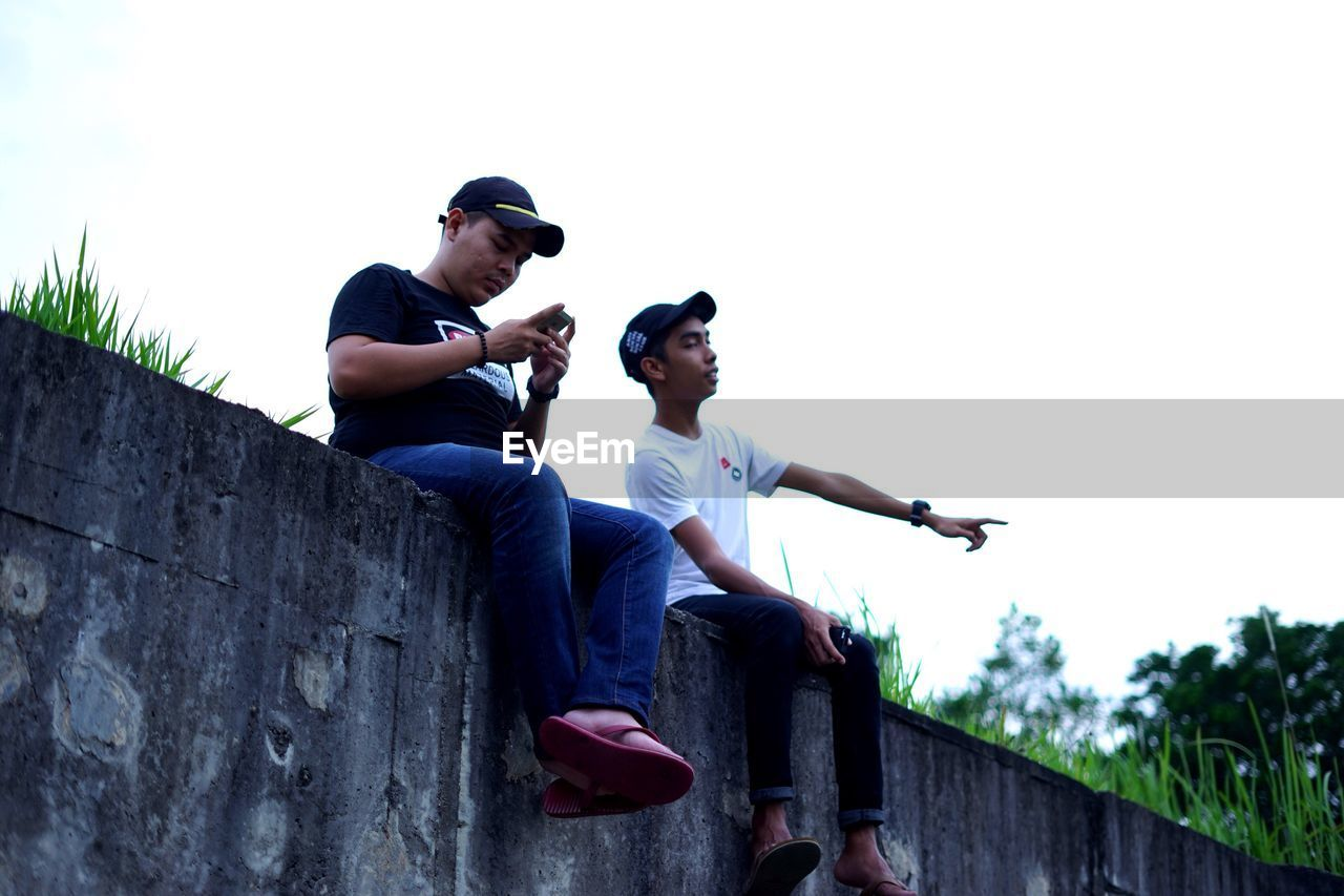 casual clothing, low angle view, leisure activity, real people, two people, young men, outdoors, cap, clear sky, lifestyles, young adult, sitting, day, full length, togetherness, bonding, sky, young women, nature, people