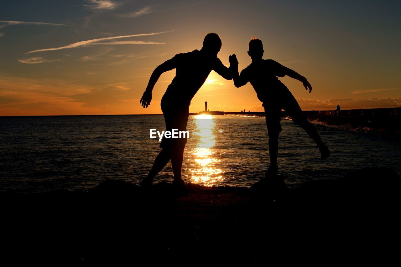 sunset, sky, silhouette, water, sea, two people, togetherness, beach, men, land, beauty in nature, real people, orange color, scenics - nature, leisure activity, horizon, lifestyles, bonding, positive emotion, horizon over water, outdoors, couple - relationship