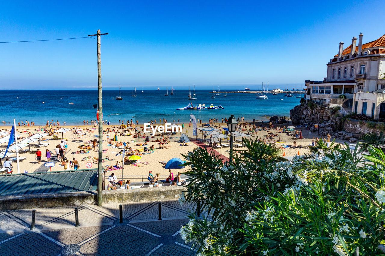 sea, architecture, building exterior, blue, built structure, outdoors, water, day, large group of people, nature, horizon over water, clear sky, sky, high angle view, real people, beauty in nature, beach, vacations, scenics, crowd, tree, city, people