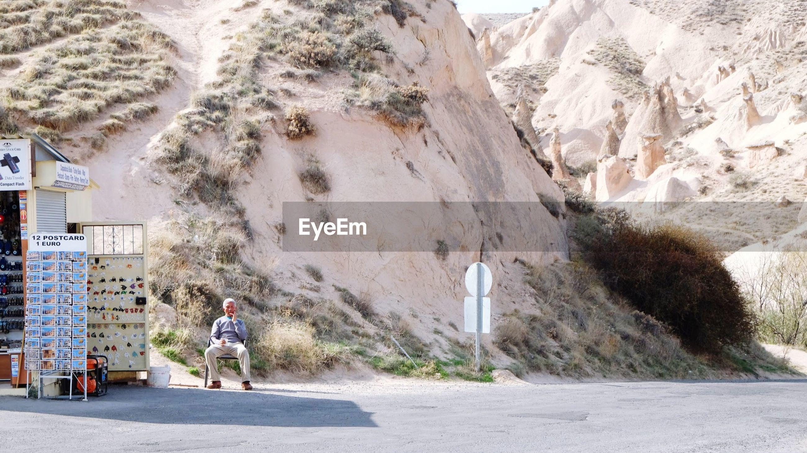MAN WALKING ON ROAD BY MOUNTAIN