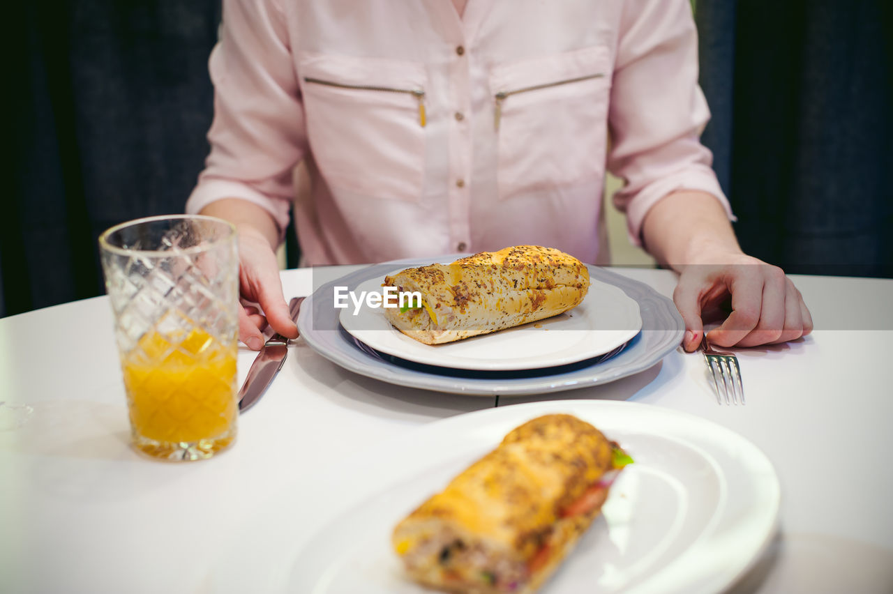 Midsection of woman by food on table