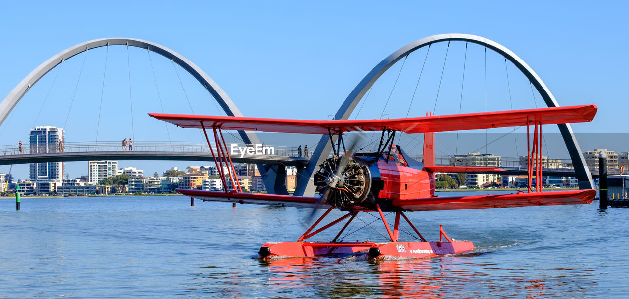 water, transportation, sky, built structure, nature, red, architecture, nautical vessel, day, waterfront, mode of transportation, no people, clear sky, travel, river, outdoors, machinery, building exterior, blue, wheel